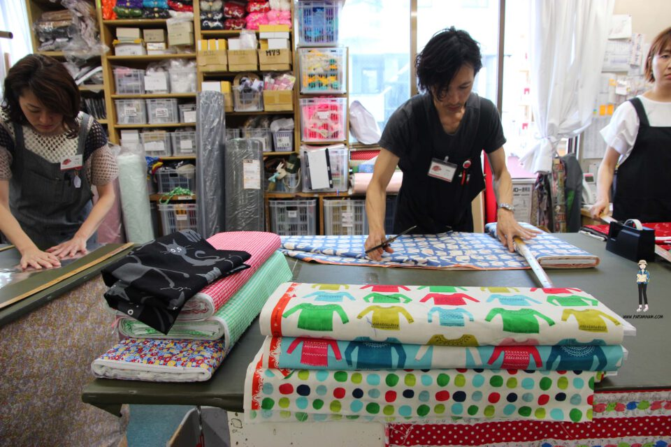 Male employees cutting cloth to sell to customers